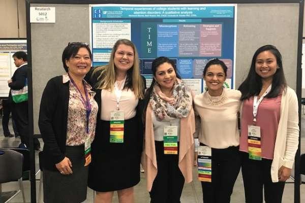 Consuelo Kreider, Mackenzi Slamka, Sharon Medina, Claudia Luna, and Jianne Apostol posing in front of a Kreider Lab research poster