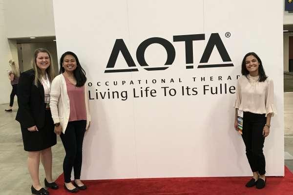Mackenzi Slamka, Jianne Apostol, and Claudia Luna posing with the AOTA red carpet backdrop